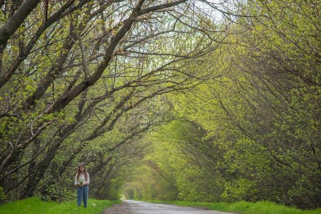 Klein meisje dat op de weg loopt met de achtergrond van groene vertakte bomen
