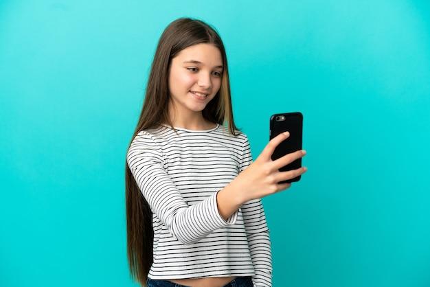 Klein meisje dat over geïsoleerde blauwe achtergrond een selfie maakt