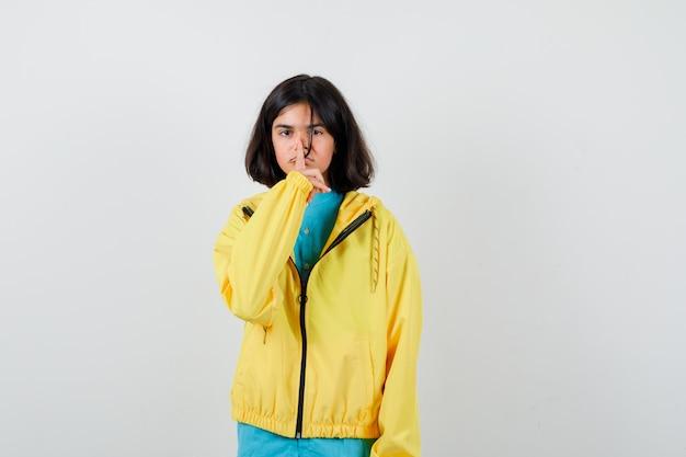 Klein meisje dat stiltegebaar in shirt, jas toont en er serieus uitziet, vooraanzicht.