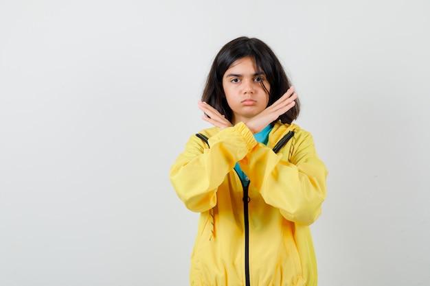 Klein meisje dat stopgebaar in shirt, jas toont en er serieus uitziet. vooraanzicht.