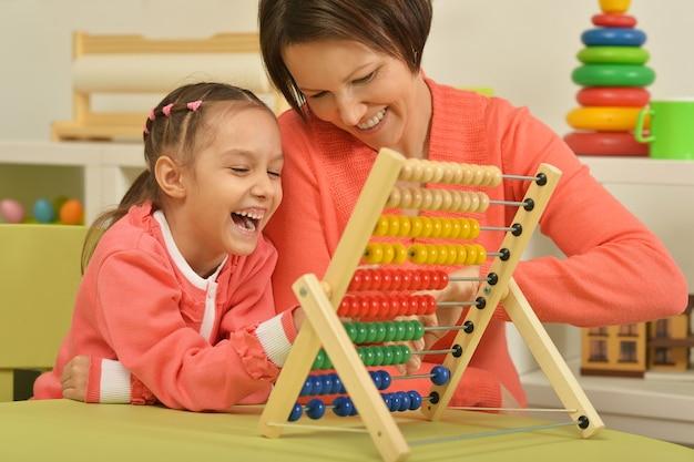 Klein meisje dat thuis wiskundeoefeningen doet met haar moeder
