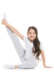 Klein meisje dat uitrekkende beenoefening doet die op witte achtergrond wordt geïsoleerd