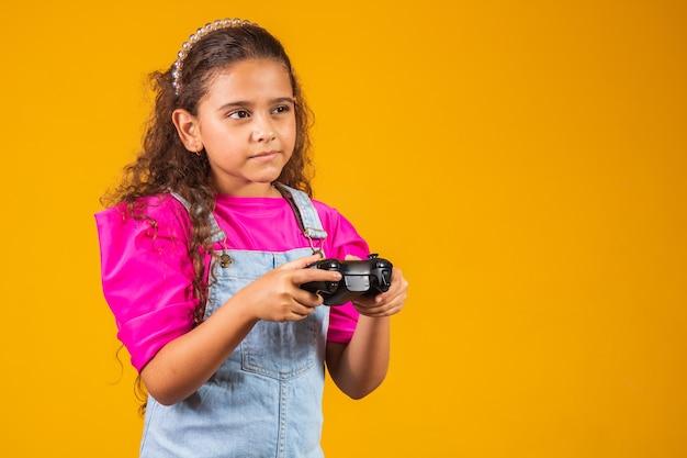 Klein meisje dat videospelletjes speelt op gele achtergrond.