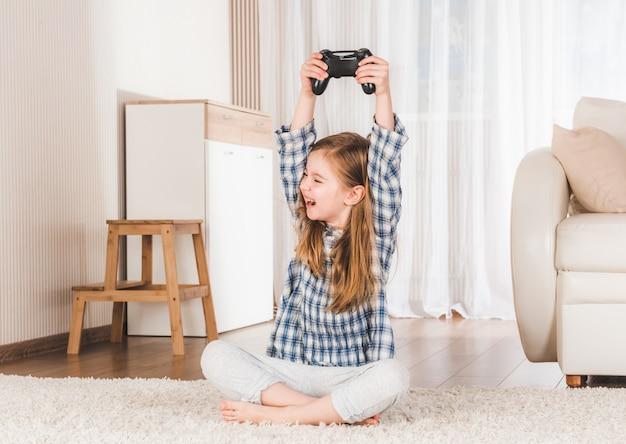Klein meisje dat vreugdevol joystick houdt