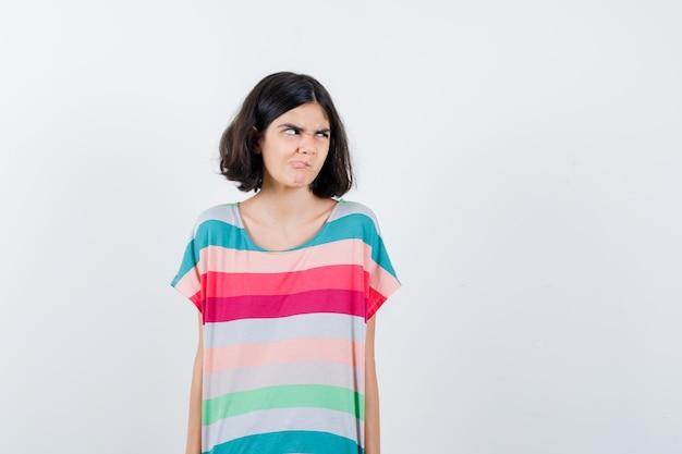 Klein meisje dat wegkijkt terwijl ze haar tong uitsteekt in een t-shirt, spijkerbroek en er ontevreden uitziet. vooraanzicht.