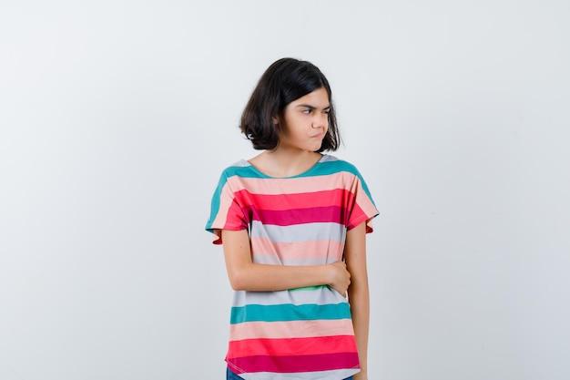 Klein meisje dat wegkijkt terwijl ze in een t-shirt poseert en er ontevreden uitziet, vooraanzicht.