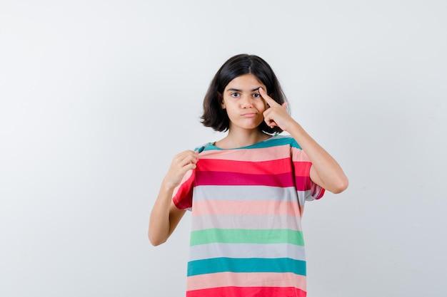 Klein meisje dat wijsvinger op oog zet, lippen in t-shirt, jeans buigt en er serieus uitziet, vooraanzicht.