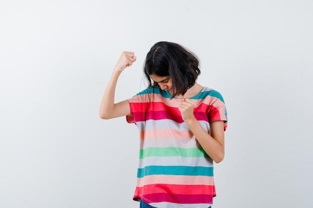 Klein meisje dat winnaargebaar in t-shirt toont en er gelukkig uitziet. vooraanzicht.