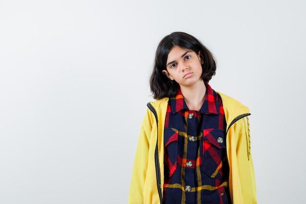 Klein meisje dat zich voordeed terwijl ze in een geruit overhemd, een jas stond en er weemoedig uitzag, vooraanzicht.