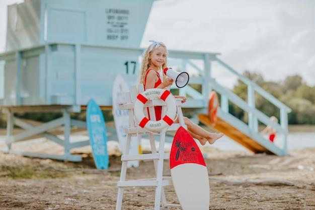 Klein meisje dat zich voordoet als badmeester op het strand