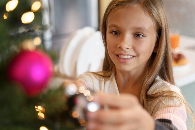 Klein meisje de kerstboom versieren
