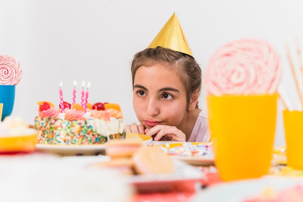 Klein meisje die partijhoed dragen die haar verjaardagscake kijken