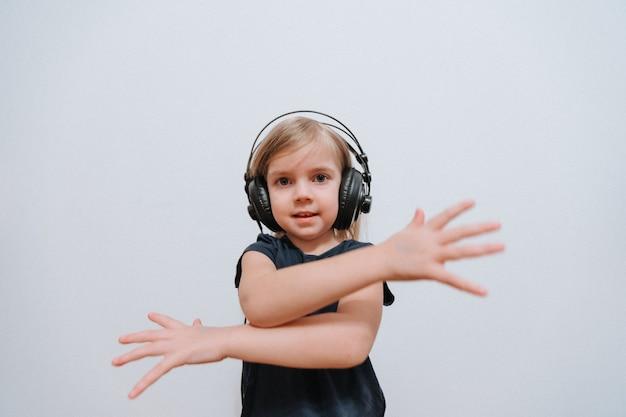 Klein meisje dj met grote koptelefoon thuis