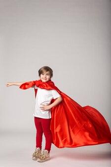 Klein meisje doet alsof supervrouw in rode cape