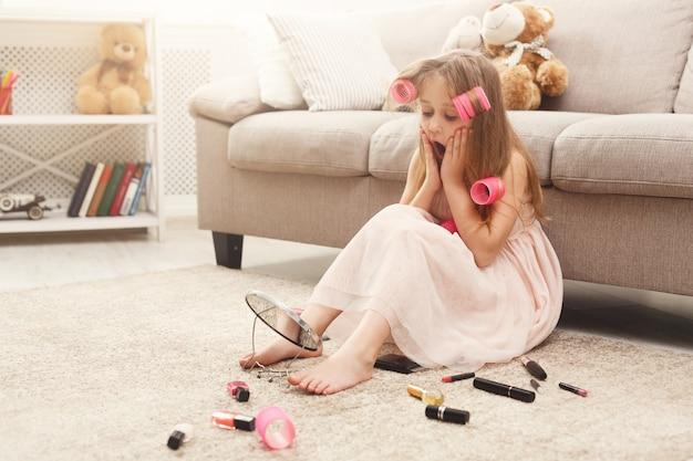 Klein meisje doet make-up met moeders cosmetica
