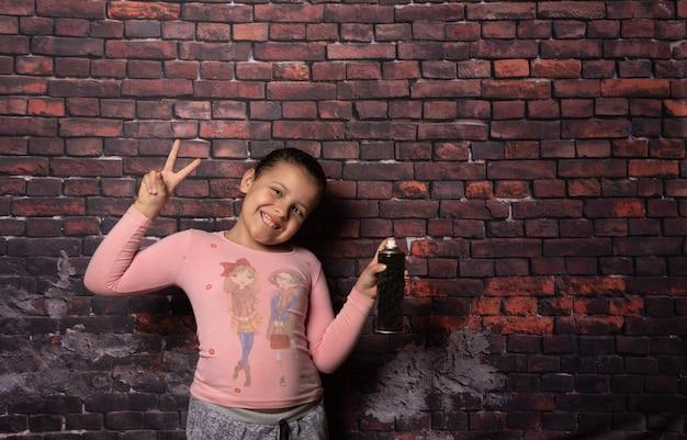 Klein meisje doet poses met een spray voor een oude bakstenen muur achtergrond, donkere achtergrond, selectieve focus.