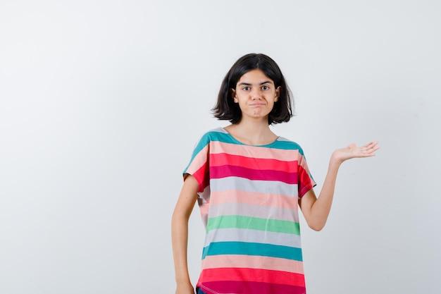 Klein meisje doet welkomstgebaar in t-shirt en ziet er zelfverzekerd uit. vooraanzicht.