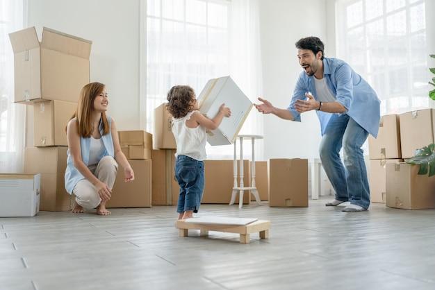 Klein meisje draagt doos naar haar vader terwijl ze dozen inpakken om naar een nieuw huis te verhuizen vader en moeder zien er gelukkig uit naar hun dochter