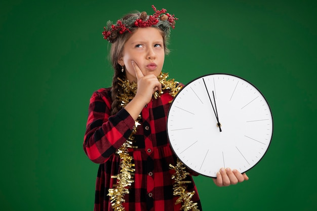 Klein meisje draagt een kerstkrans in een geruite jurk met klatergoud om de nek en houdt een wandklok vast die verbaasd opkijkt terwijl ze over de groene muur staat
