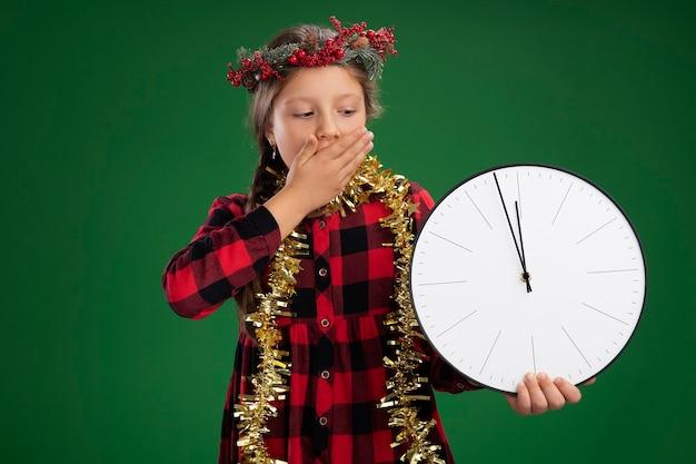 Klein meisje draagt een kerstkrans in een geruite jurk met klatergoud om de nek met een wandklok die ernaar kijkt en geschokt is en de mond bedekt met de hand die over de groene muur staat
