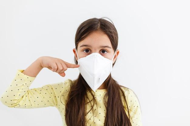 Klein meisje draagt een masker op een witte achtergrond, een meisje met een medisch beschermingsmasker covid-19 of coronavirus van een geïnfecteerde persoon, corona beschermd help beschermen voor wereld en mensen stop viruswaarschuwing