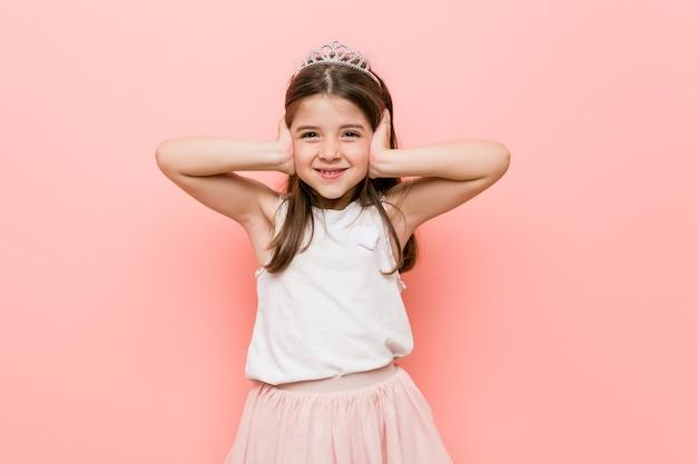 Klein meisje draagt een prinses-look die oren bedekt met handen en probeert niet te hard geluid te horen.