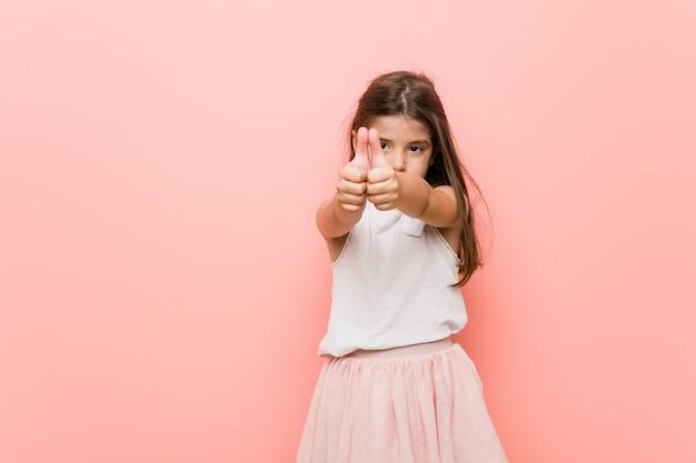 Klein meisje draagt een prinses-look met duimen-ups, proost over iets, ondersteunt en respecteert concept.