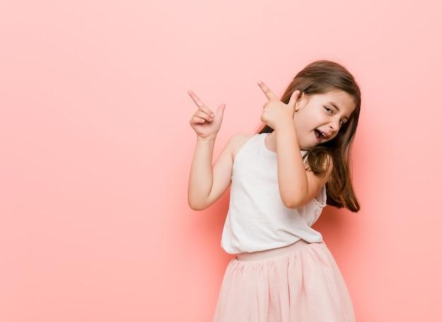 Klein meisje draagt een prinses look wijzend met wijsvingers naar een kopie ruimte, opwinding en verlangen uitdrukken.