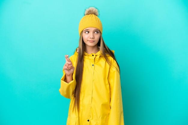 Klein meisje draagt een regendichte jas over geïsoleerde blauwe achtergrond met vingers die kruisen en het beste wensen