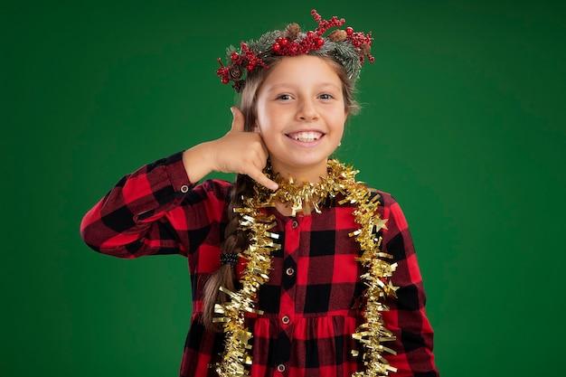 Klein meisje draagt kerstkrans in geruite jurk met klatergoud om nek, blij en positief en maakt me een gebaar dat over groene muur staat