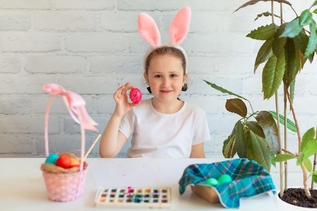 Klein meisje draagt konijnenoren en schildert eieren voor paasvakantie