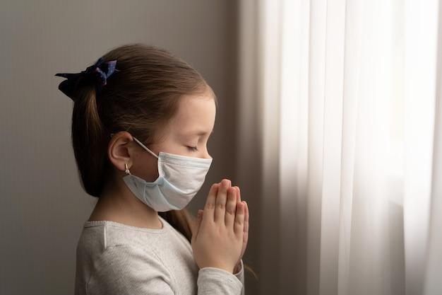 Klein meisje draagt masker ter bescherming van covid-19. ze bidt 's ochtends voor een nieuwe dag vrijheid tegen het wereldcoronavirus. kleine meisje hand bidden voor god danken