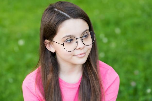 Klein meisje draagt vintage rand brillen groene gazon achtergrond, ogen gezondheid concept.
