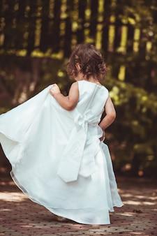 Klein meisje draait rond in sierlijke jurk buiten
