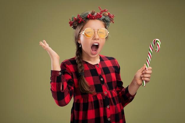 Klein meisje dragen kerstkrans in ingecheckte jurk bedrijf candy cane kijken camera blij en opgewonden schreeuwen verhogen arm permanent over groene achtergrond