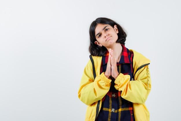 Klein meisje drukt de handen samen om te bidden in geruit hemd, jasje en ziet er hoopvol uit, vooraanzicht.