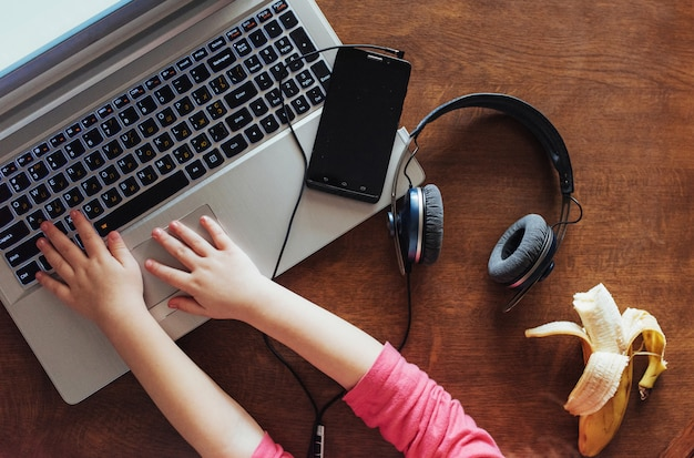 Klein meisje drukt op het toetsenbord van zijn laptop