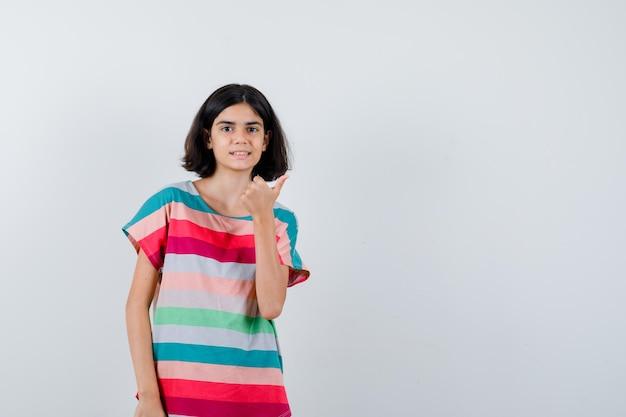 Klein meisje duim opdagen in t-shirt, jeans en er gelukkig uitzien. vooraanzicht.