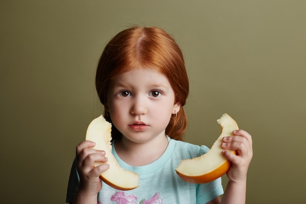 Klein meisje eet een meloen