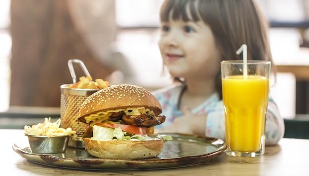 Klein meisje eet in een fastfood-café