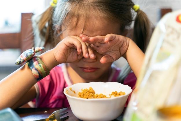 Klein meisje eet thuis in de keuken en gril