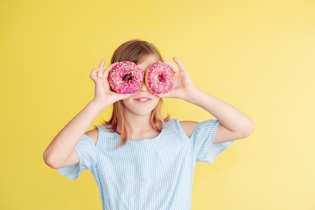 Klein meisje en donuts. leuke sfeer. grappige gezichten