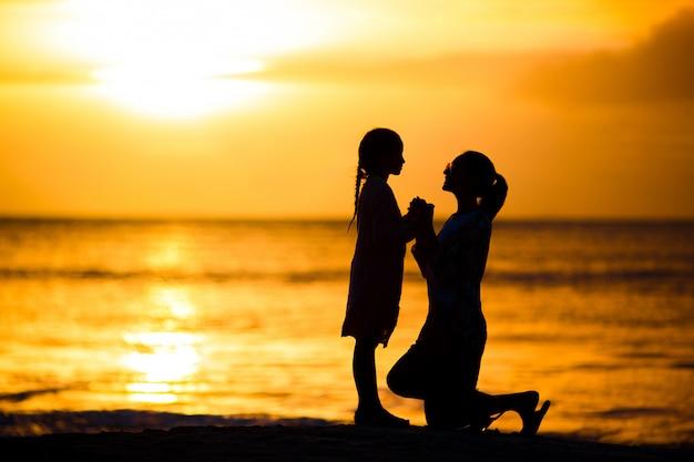 Klein meisje en gelukkig moedersilhouet in de zonsondergang bij het strand