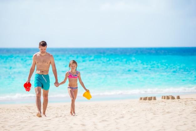 Klein meisje en gelukkige papa spelen op het strand