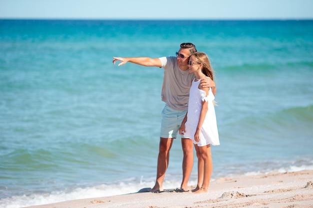 Klein meisje en gelukkige vader die plezier hebben tijdens strandvakantie