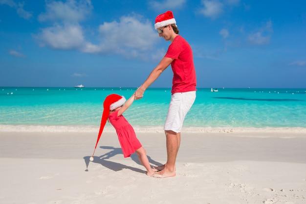 Klein meisje en gelukkige vader in santa hat hebben plezier op tropisch strand