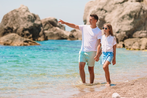 Klein meisje en gelukkige vader plezier tijdens strandvakantie