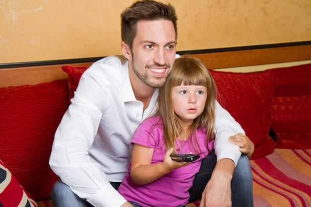 Klein meisje en haar broer genieten van het eten van popcorn en tv kijken