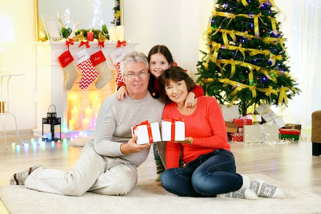 Klein meisje en haar grootouders in de woonkamer ingericht voor kerstmis
