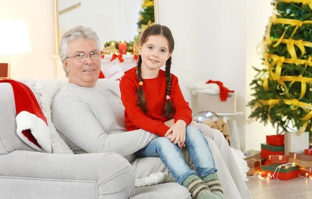 Klein meisje en haar grootvader zittend op de bank in de woonkamer ingericht voor kerstmis